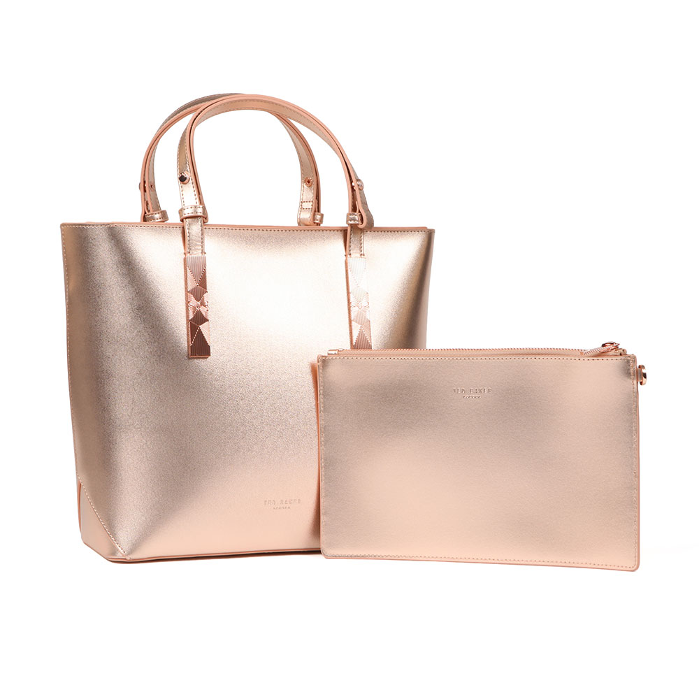 Ted Baker Jaceyy Adjustable Handle Zip Shopper in 'rose gold' has been crafted with a striking metallic finish in a smooth bovine leather. The sleek, tall design features short twin handles that ensure a sophisticated look and a top zip fastener ensures safe storage. Rose gold hardware and Ted Baker London printed branding finishes the look. A matching rose gold clutch bag is also included. Approx: H: 26cm x W: 30cm x D: 11cm Clutch: H: 16cm x W: 25.5cm